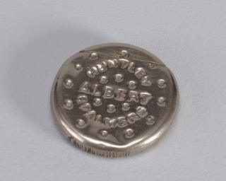 "A circular metal matchsafe. The front is decorated with a border of dots and the logo ""Huntley Albery & Palmers"""