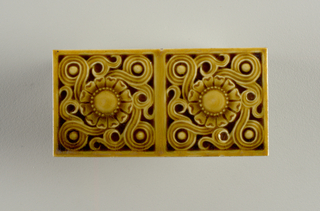 Rectangular molded tile of white clay. Face of tile shows pair of joined tile faces decorated with pair of joined rosettes surrounded by scrolling tendrils and framed in a plain band frame. Tile glaze mustard yellow.