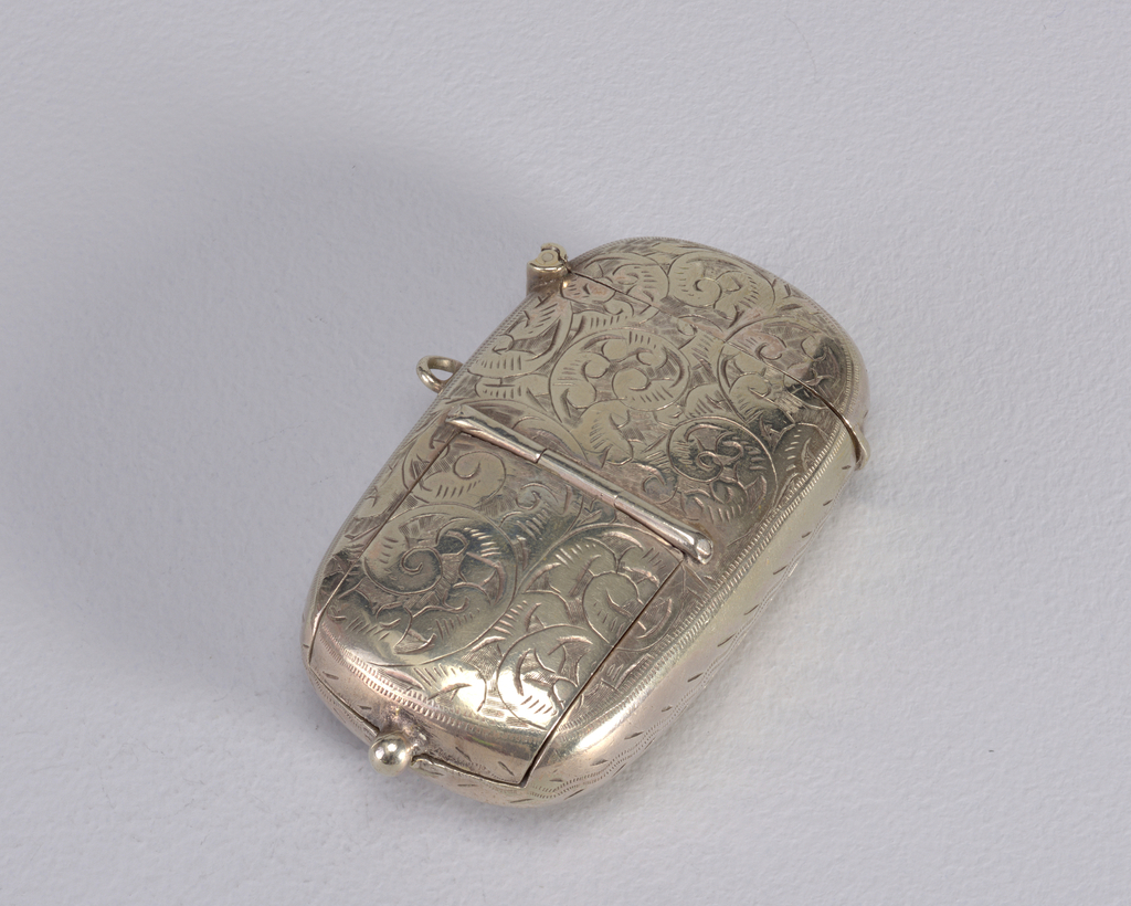 Oblong, curved sides and corners, featuring overall incised, decorative scroll pattern, front reveals coin compartment hidden beneath cover located at lower half, hinged at center, with thumb catch at bottom, stamps may be stored on underside of compartment cover; revealed when matchsafe lid is opened at top are 2 long metal cylinders vertically recessed inside (possibly for pencil and toothpick), reverse of box has same overall decorative pattern with open, circular reserve at center, link on side. Lid hinged on side. Striker recessed in top of lid.