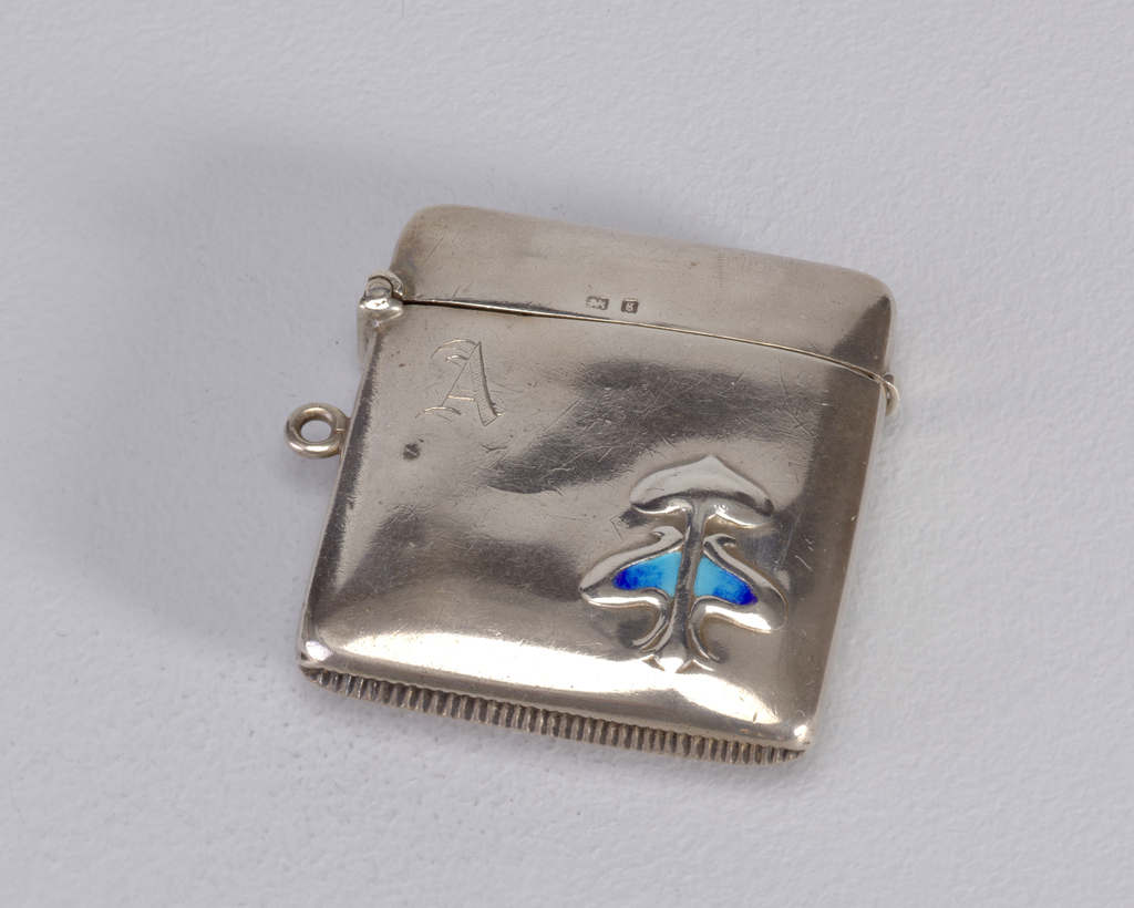 """A silver square matchsafe with rounded corners. Below the opening, the letter """"A"""" is stamped and in the lower right-hand corner is an abstract design with blue accent."""