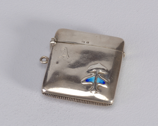 "A silver square matchsafe with rounded corners. Below the opening, the letter ""A"" is stamped and in the lower right-hand corner is an abstract design with blue accent."