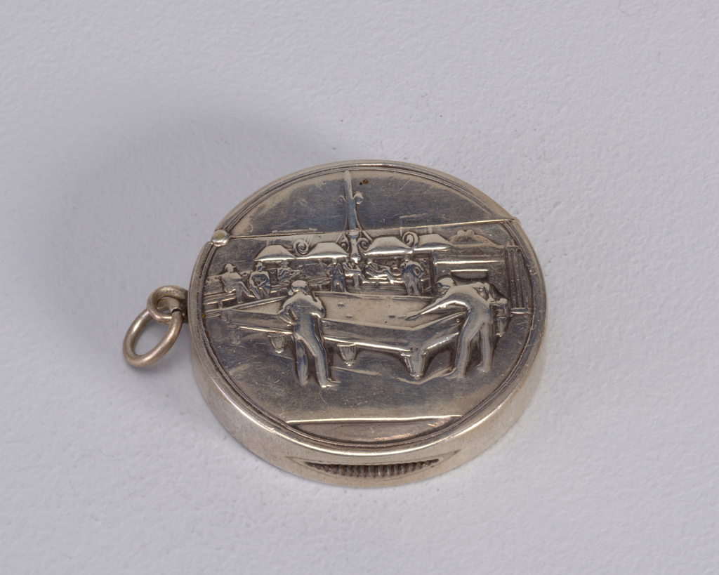 Circular, featuring raised decoration of  2 men playng billiards in a game room, other men seated in background. Link attached to left side. Box bisected near top and lid hinged on upper left. Striker on bottom.