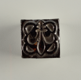 "A square molded tile of white clay; on the reverse is a series of seven strips alternately impressed and raised, on the fifth strip is embossed: ""Robertson"". Face of the tile is decorated with a four-leaf snow-flake like design set with plain narrow borders. Tile is glazed a purple-brown crackle glaze."