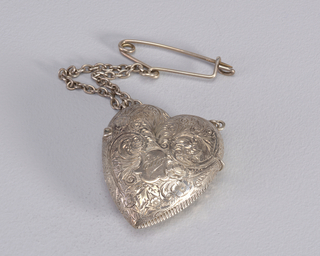 "In the form of a heart, featuring intricate, all-over incised decoration of swirling scroll forms, flowers and foliage. Small central reserve inscribed ""Etta"". Identical reverse reserve inscribed ""1898"". Long chain attached to links on lid, pin attched to top of chain. Lid hinged on side, thumb catch on opposite side. Striker in recessed groove on lower right side of box."