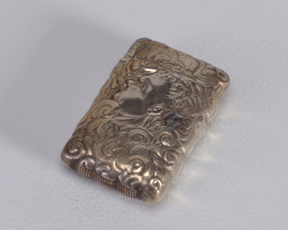 Rectangular, rounded corners and sides, featuring raised decoration of hand holding a cigar amid smoke swirls that decorate entire surface. Reverse features male in profile, blowing smoke, his curly hair blending in amid smoke swirls that decorate entire surface. Lid hinged on side. Striker on bottom.