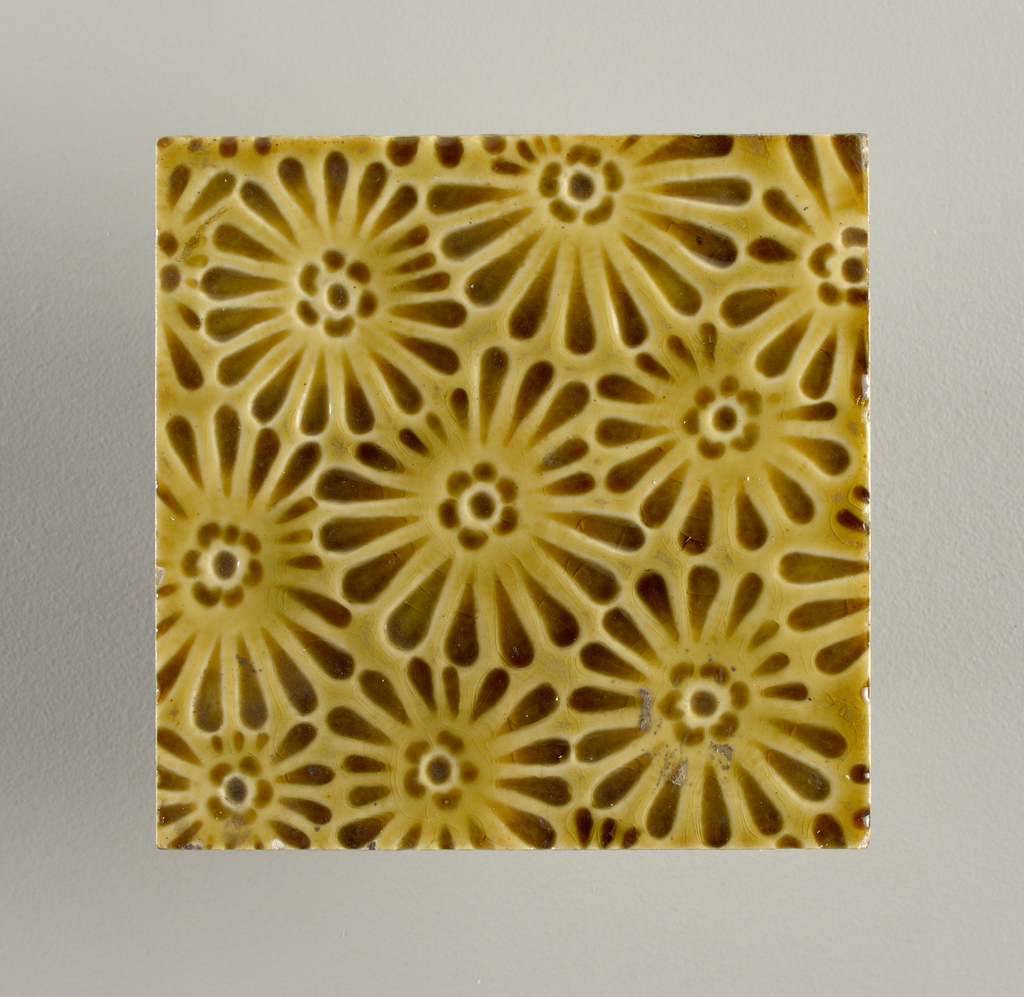 """Molded, square tile, white clay; impressed on reverse with inscription: """"J. & J.G. Low, Patent Art Tile, Works, Chelsea, Mass. U.S.A."""" Face of tile impressed with all-over pattern of stylized daisies deep, honey-brown glaze."""