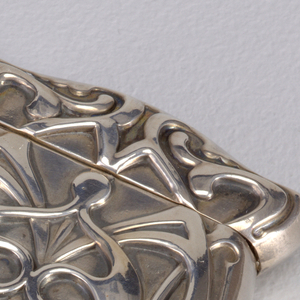 Oblong, with rounded corners, sloping sides, curved top and bottom, featuring stylized, intertwined tendrils in abstract motif, identical on both front and reverse. Lid hinged on side. Metal pinched and grooved on front and reverse at bottom to form striker.