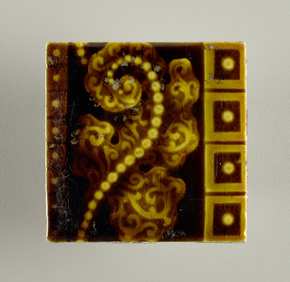 """A square, molded tile of white clay; tile back impressed with two concentric circles with """"Trent"""" embossed in center. Tile is decorated with a beaded leaf figure framed with horizontal bands of bead-centered blocks; molasses brown crackle glaze."""
