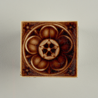 Square molded tile made of white clay; reverse has pair of concentric rings embossed, no inscription; face is decorated with stylized five-petal rosette framed in plain circle; corners have flowers fitted into triangular ground; purple-brown crackle glaze.