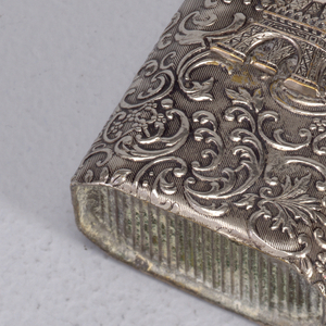 Oblong, 8 sided box, with continuous raised scroll work and floral ornament on all sides, front features superimposed Eiffel Tower on decorated field. Thin, flat lid hinged on upper right. Striker recessed in bottom.