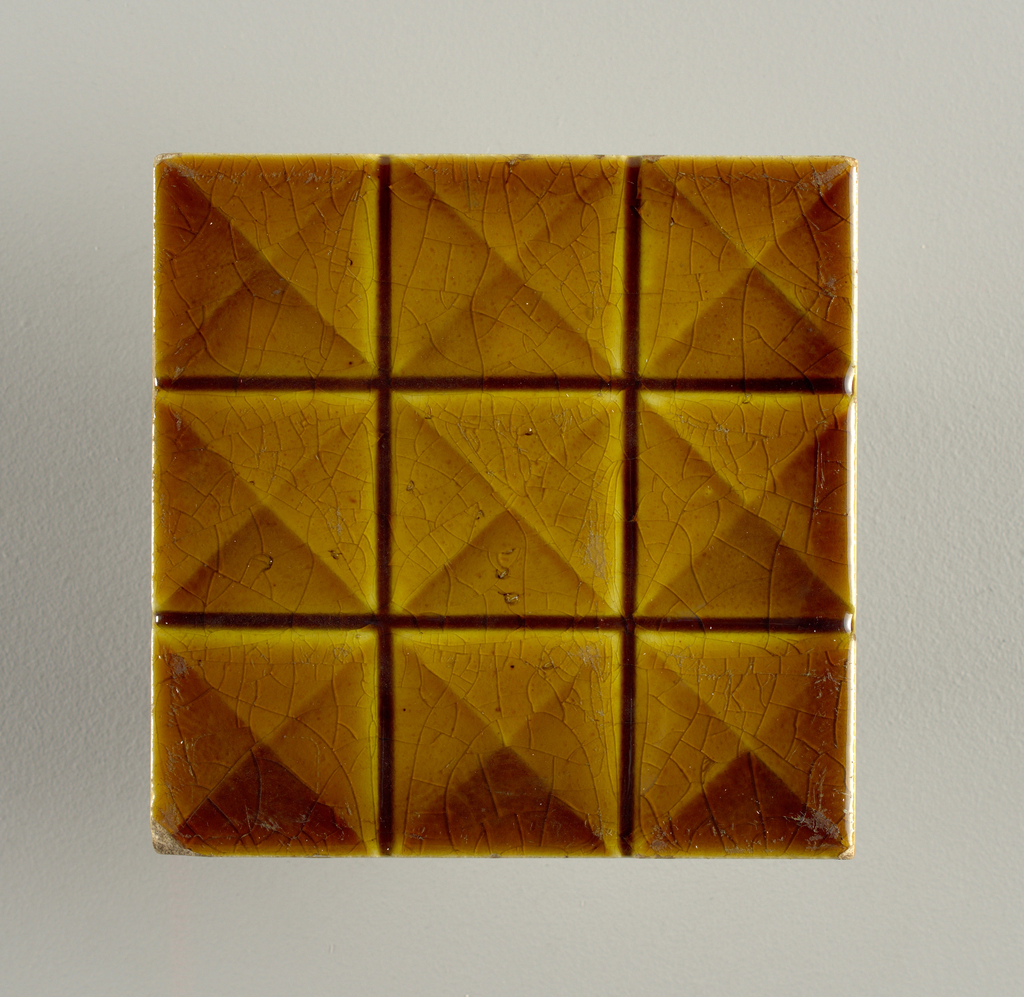 """Molded, square tile of white clay. Reverse has series of nine horizontal bars alternately raised and depressed, center inscribed: """"Trent"""". Tile face divided into gird of three rows of three squares each; squares divided into four equilateral triangles; honey-brown crackle gaze."""