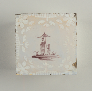 "Square tile. Grayish white ground centered with manganese figures in the Chinese style, of a woman and boy holding parasol, both figures standing on a low mound. Bordered with crude floral ornament in overglaze white. Example of ""bianco sopra bianco"" technique."