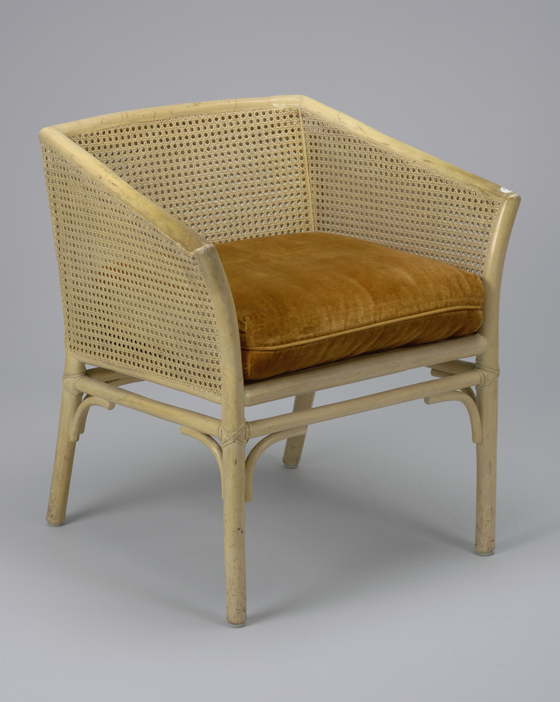 This double caned armchair was inspired by the classic French upholstered Bergére.  The chair's legs taper inwards and are supported by a rounded front stretcher.  Brownish-red velvet upholstery covers the seat.  The caned seat back and sides are contigious with the crest rail and arm rests.