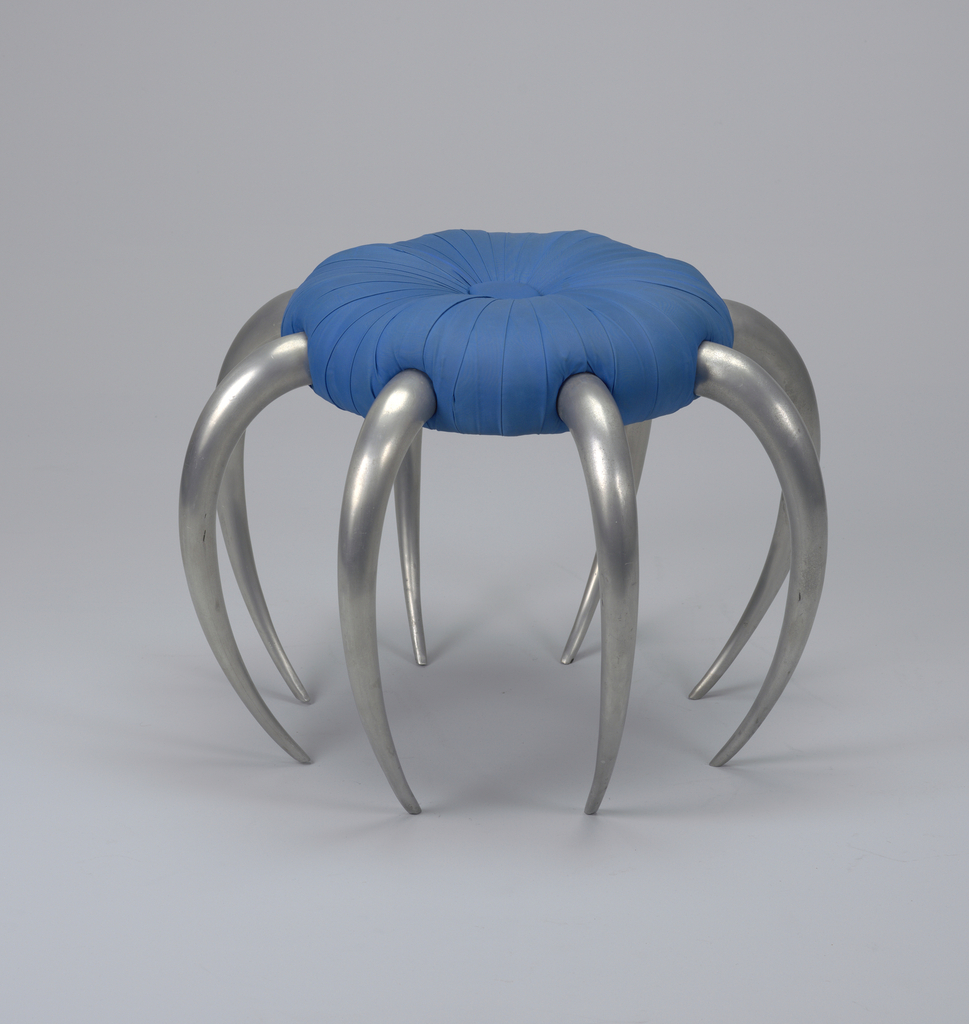Circular seat upholstered in bright blue textile; large blue textile covered botton in center; eight in-curved aluminum legs tapering to pointed feet.