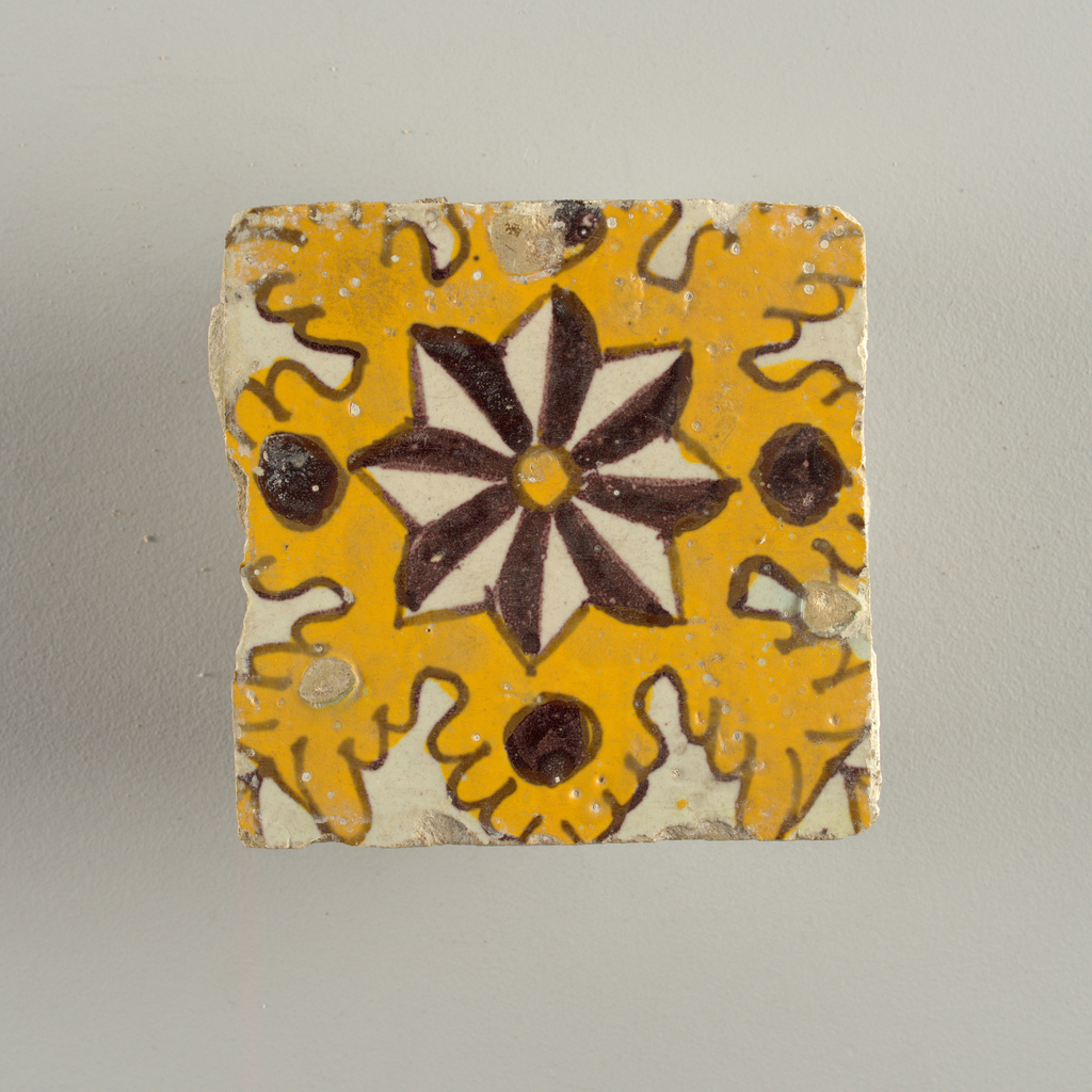 Tile of glazed earthenware- yellow, brown and white with star motif.