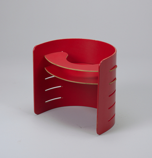 Child's semi-circular chair in red-painted plywood; pierced with slats allowing for adjustable flat seat and additional parts to be removed and reinserted at various hights.