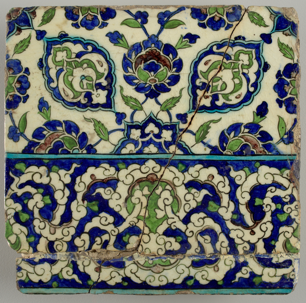 Border tile decorated in white, cobalt, turquoise, apple-green, and purple with black lines. Lower part forms part of a continuous arabesque frieze featuring interwoven cloud bands. Upper half composed of two quadrants of a four quadrant repeating design, make up of a system of conventionalized blossoms, leaves, stems, and arabesques in shaped cartouches.