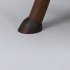 Contoured ovoid seat on three out-curved columnar legs with hoof-like feet.