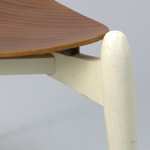 Curved triangular plywood seat on white-painted tripod base with three tapering legs.
