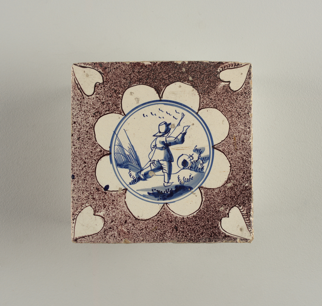 Square tile with octofoil rosette centered with double walled circle enclosing landscape with shepherd and staff, facing right, in cobalt blue. Ground stippled manganese violet. Heart-shaped reserves at corners with short curved lines along one side.