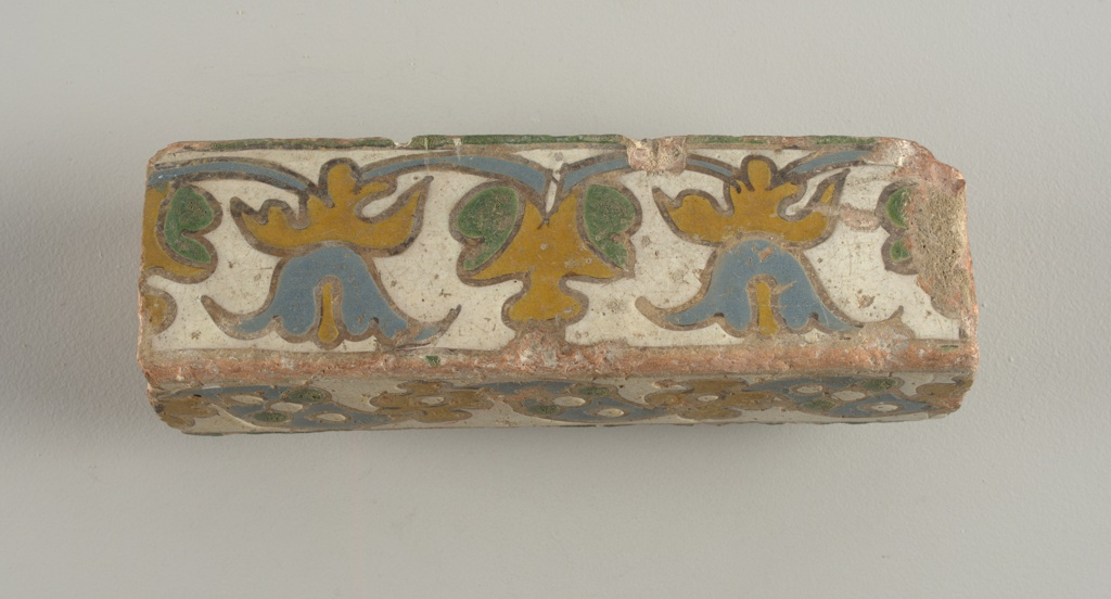 Rectangular in sections. Glazed on one broad and one narrow face with simple foliate patters in cuerda seca techinique, simulating mosaic faience.