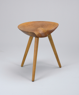 Semi-circular contoured, concave seat on three splayed, tapering legs.