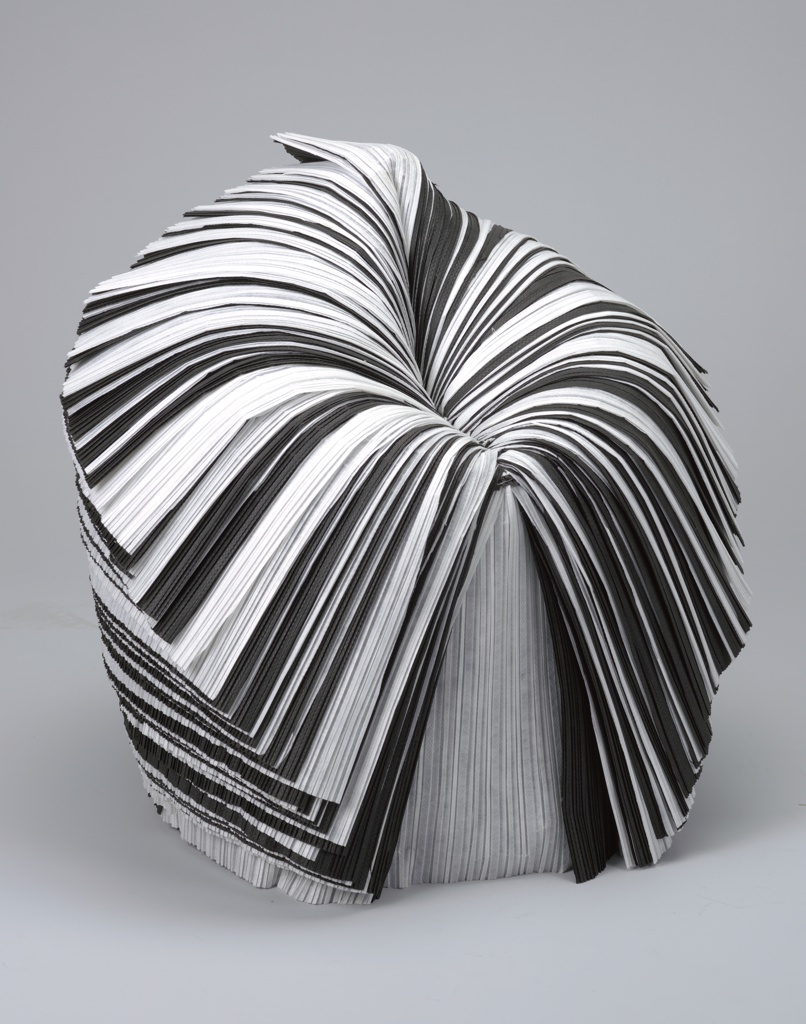 Roughly ovoid form made from a black and white roll of pleated waste paper, the upper portion vertically slit at front center, the resulting layers peeled down to form the chair seat and peaked back.