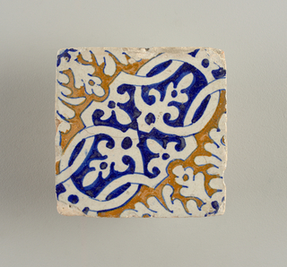 Portion of a design composed of strap work and conventionalized foliage; painted in blue and brown.