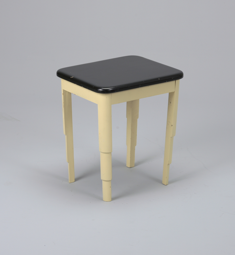 Lacquered square-topped stool with tapered and stepped legs.