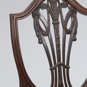 Shield-shaped back.  The vase shaped openwork vertical splat consists of five curved vertical slats-- the center one is carved with foliage at the base; the branches into three ostrich feathers.  Splats on both sides curving outwards meet those on the outside in two rosettes, from which swags of drapery hang.  The front legs are moulded and slightly tapered.  Front seat rail is serpentine and side rails are bowed slightly.  There is a drop in seat covered in silk solid cut stamped cloth velvet.