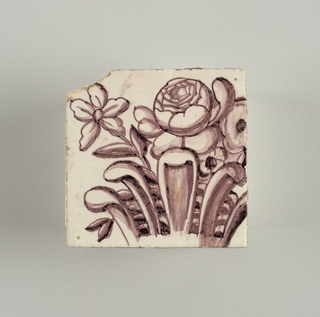 Tile from upright rectangular panel of tiles; dark purple (manganese) on white ground showing arched framework; oval cartouche bearing double monogram (probably Lubert Adolf Torck), supported by pair of nude amors; pair of small amors holding crown above, borne by pair of female terms; surrounded by leafscrolls and foliations, with pair of flower-filled urns; top center, lunetted amor's head pendented with rosetted lattice cartouche.  To be used in Rozendaal Castel. Intended to be viewed inset into a wall- indicated by the inclusion of a trompe-l'oeil marbleized edge that surrounds three sides of the panel.