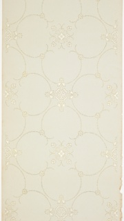 Large beaded quatrefoils with small five-petal flower motif and fleuron insets connected by larger fleurons. Printed in white liquid mica and gold liquid mica on pale blue ground.