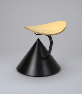 Concave oval plywood seat on curved black tubular metal support rising from side of large, conical black metal base.