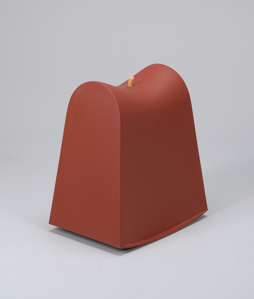 Tapered, red, molded block-like form with concave seat reminsicent of a saddle and curved base for rocking; finger-like projection in center of seat.