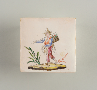 Cream-colored clay slightly corrugated on reverse. White glaze, of which traces are shown on reverse. Decorated with figure of a man carrying a basket, wearing a Chinesque cap.
