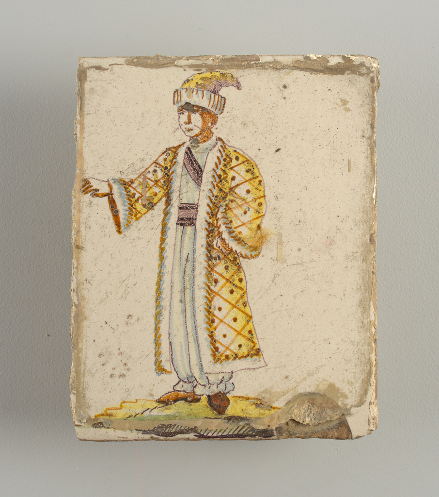 Standing man, dressed in long white trousers, fur trimmed yellow coat and headdress; his right arm slightly raised. Chinoiserie type of decoration.