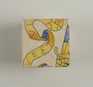 Square tile with portion of a larger decorative scheme, showing part of banderole with letters...USET..., VE...AX, and part of a hand in mailed glove grasping a sword. Outlines and letters in blue; objects in yellow shading into orange.