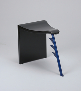 Undulating black triangular seat; blue tubular metal leg with three shaped projections at apex, vertical black panel as leg at rear.