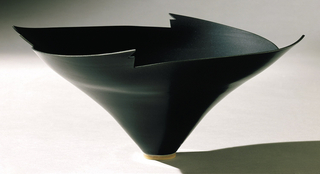 Thrown porcelain bowl. From narrow (4.3 cm diameter) circular foot, body flares upward and outward at extreme angle.  Upper edge cut with four wing-like notches.  Overall surface smooth, with modulations.  Exterior and interior with semi-matte black glaze; foot ring glazed orange-brown outside.