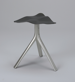 Rippled triangular black iron seat mounted on matt silver-colored aluminum tripod base.