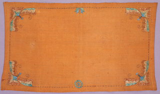"""Light reddish-brown linen table mat with a stylized moth embroidered in brown, blue and green in each corner, facing the center of the cloth.  A signature """"D"""" is embroidered within a wheel at bottom center."""