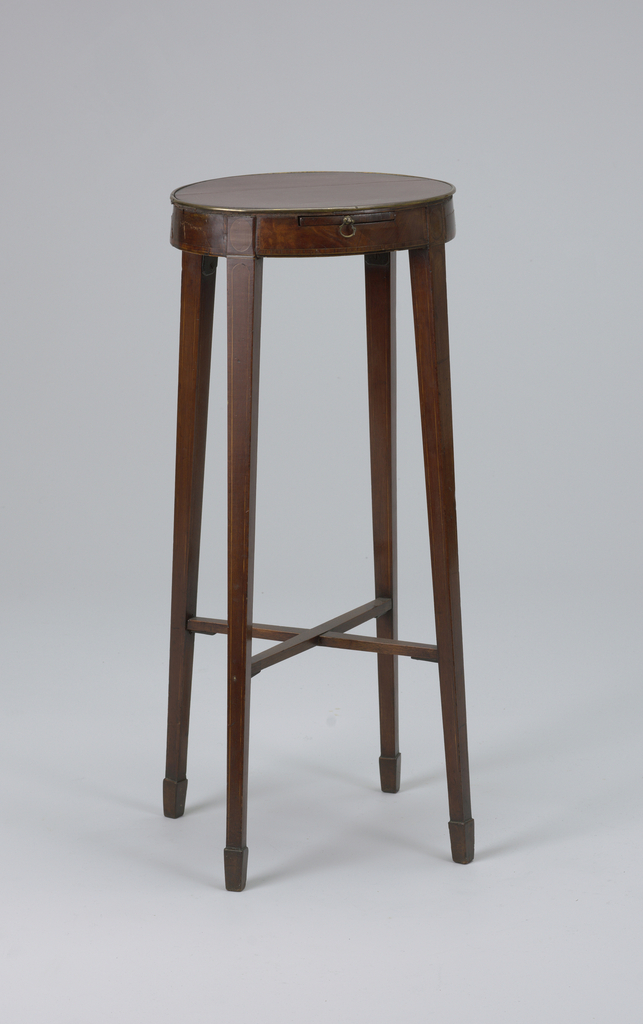 Oval top edged with brass strip inlaid; rectangular slide with small brass handles. Square tapering legs splayed outward, ending in spade feet joined by X-frame stretchers. Legs have stainwood line inlay; frieze has satinwood line inlay, crossbanding of harewood, and small medallions of harewood inlaid above each leg. (Stretchers possibly replaced?)