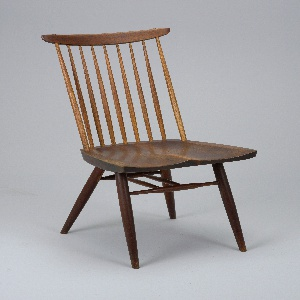 Wooden chair with splayed legs and front and back stretchers connected by two additional stretchers. Back of nine vertical splats topped with slightly curved horizontal crest rail. Seat contoured for sitting.
