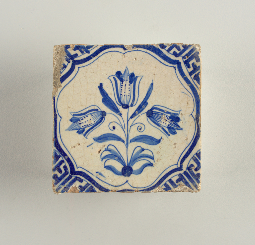 Cobalt blue on white ground. Conventionalized plant design of three tulips on single leafy stem within a circular scrolled cartouche extending to edges. Fret ornament in corners.
