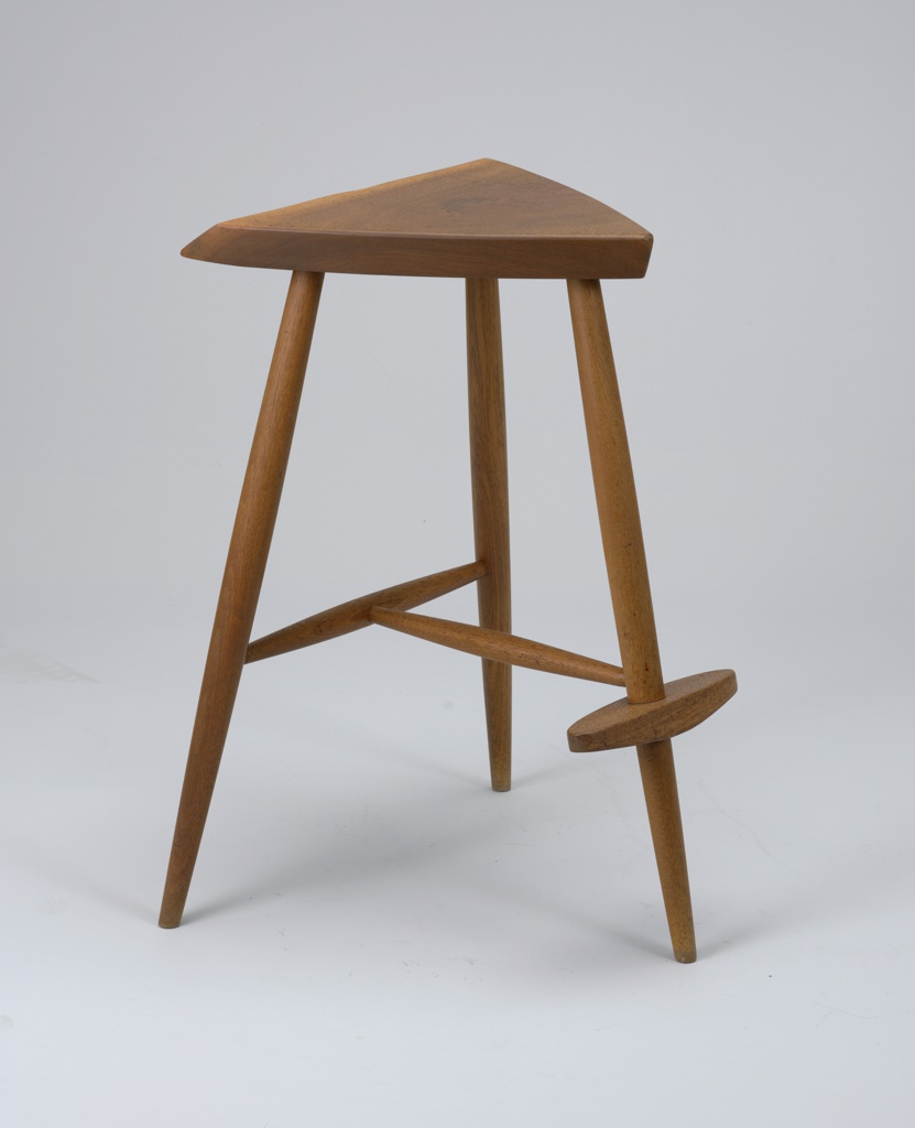 Thick triangular seat mounted on three tapering cylindrical legs; narrow foot-rest on front leg; stretcher between rear legs.