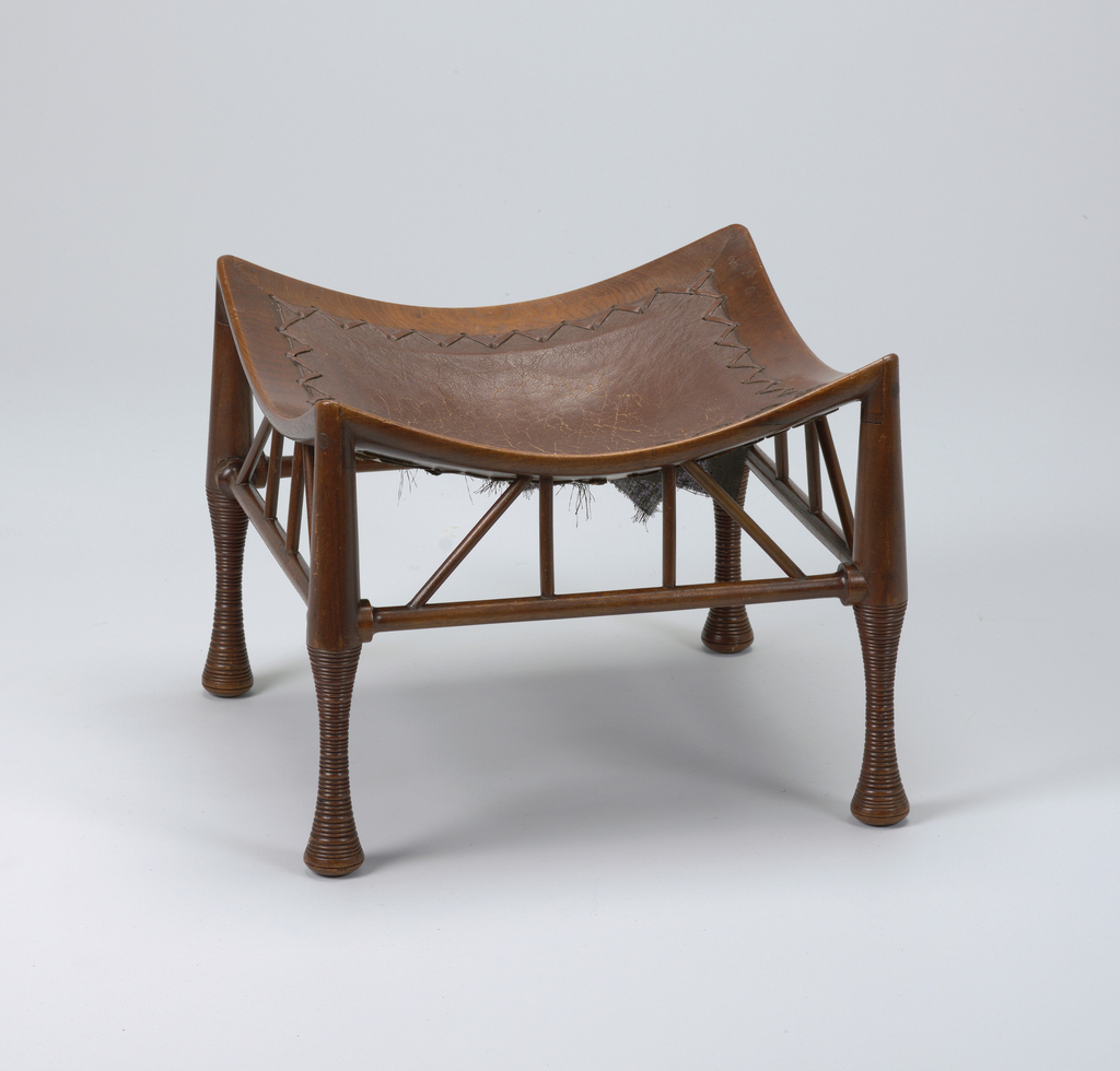 Square, concave brown leather seat in wood frame with tapering cylindrical legs joined by horizontal stretchers and angled dowls.
