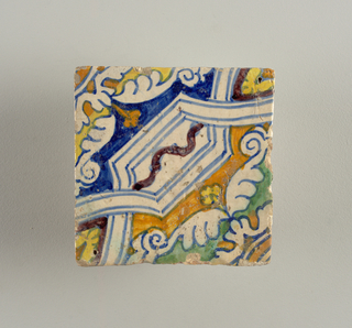 Portion of a design composed of strap-work, painted in blue, yellow, green, brown, and violet.