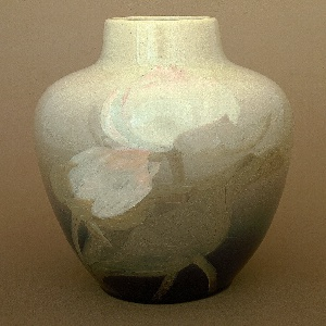 Cast white clay body.  Ovoid body with raised neck; no foot.  Underglaze slip-decorated on front with two large unopened lotus blossoms with water leaves and single blossom with unfurled leaf and stem on side.  Blossoms are pastel pink and leaves are a pale gray-green. Background shades from a dark blue to a pale green at shoulder.  Allover clear high glaze with wide crackle. Bottom glazed.
