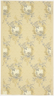 Circular motifs connected by blue floral vining. Background of simplified spaced-out flowers. Ground is beige. Printed in blue, gold mica, silver mica, cream, and grey. 
