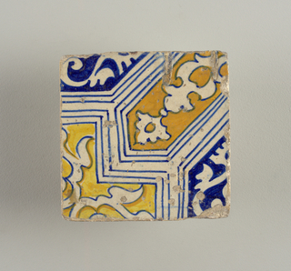 Portion of a design composed of geometrical shapes enclosing conventionalized foilage; painted in blue, yellow, and brown.
